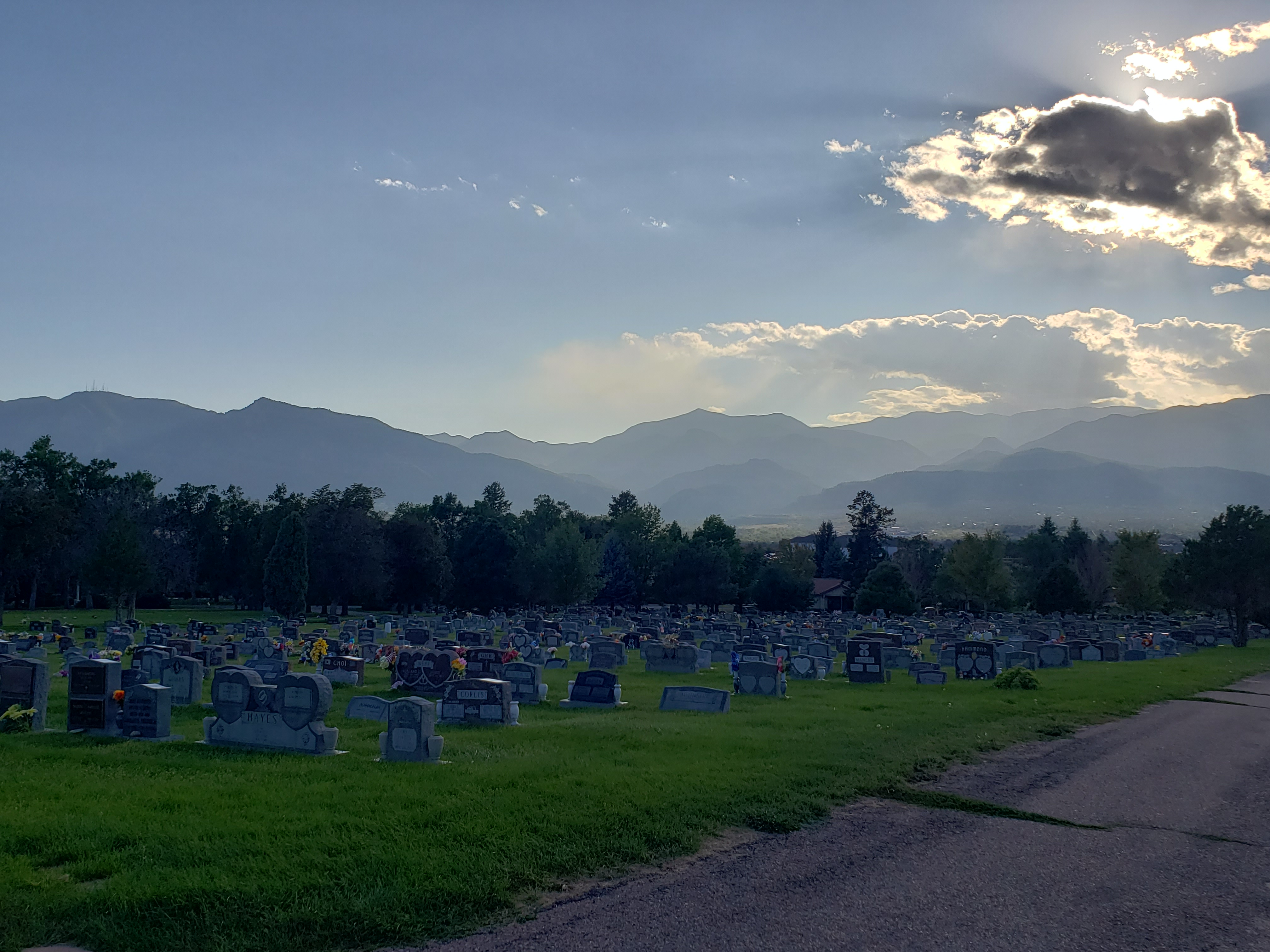 Evergreen cemetery: rows of headstones with trees and mountains in the background