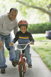 Dad with son learning to ride a bike.