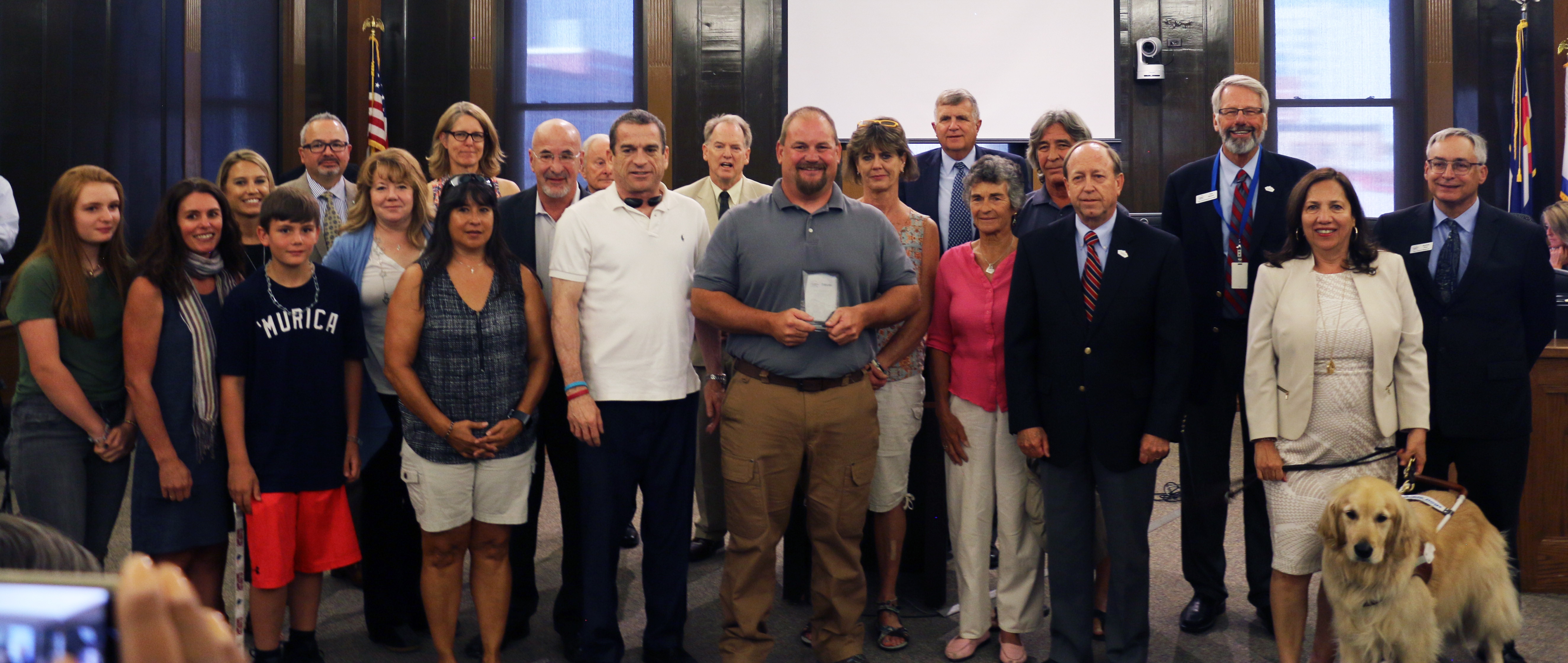Cris Barnhart with award surrounded by mayor, city council and members of the community