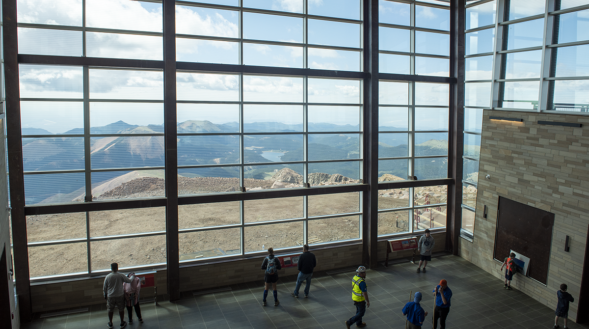 a multi story wall of windows frames the mountainous landscape outside. People take in the view from the floor below and look very small in front of the grand view.