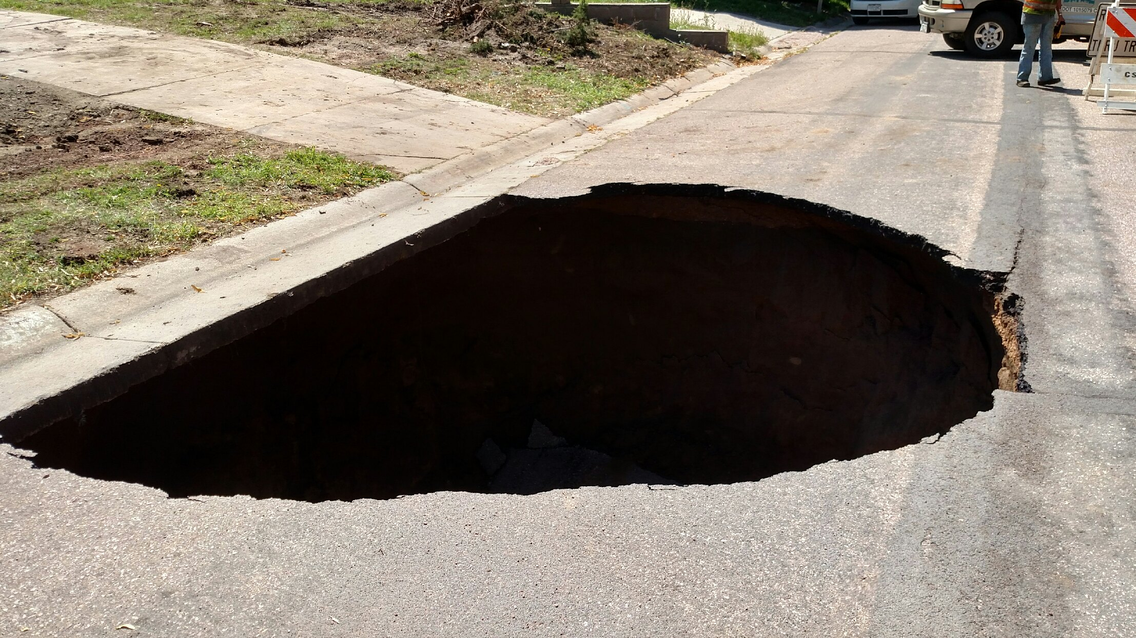 photo of large sinkhole taking up one lane of a street