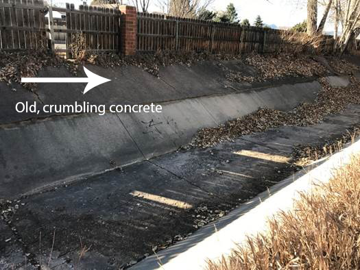 Old stormwater channel with crimbling concrete and debris. Old, crumling concrete extends all the way to the top of the channel.