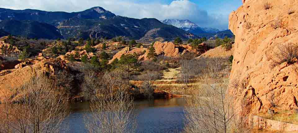 A pond in Red Rock Canyon Open Space surrounded by red rocks, trees and mountains