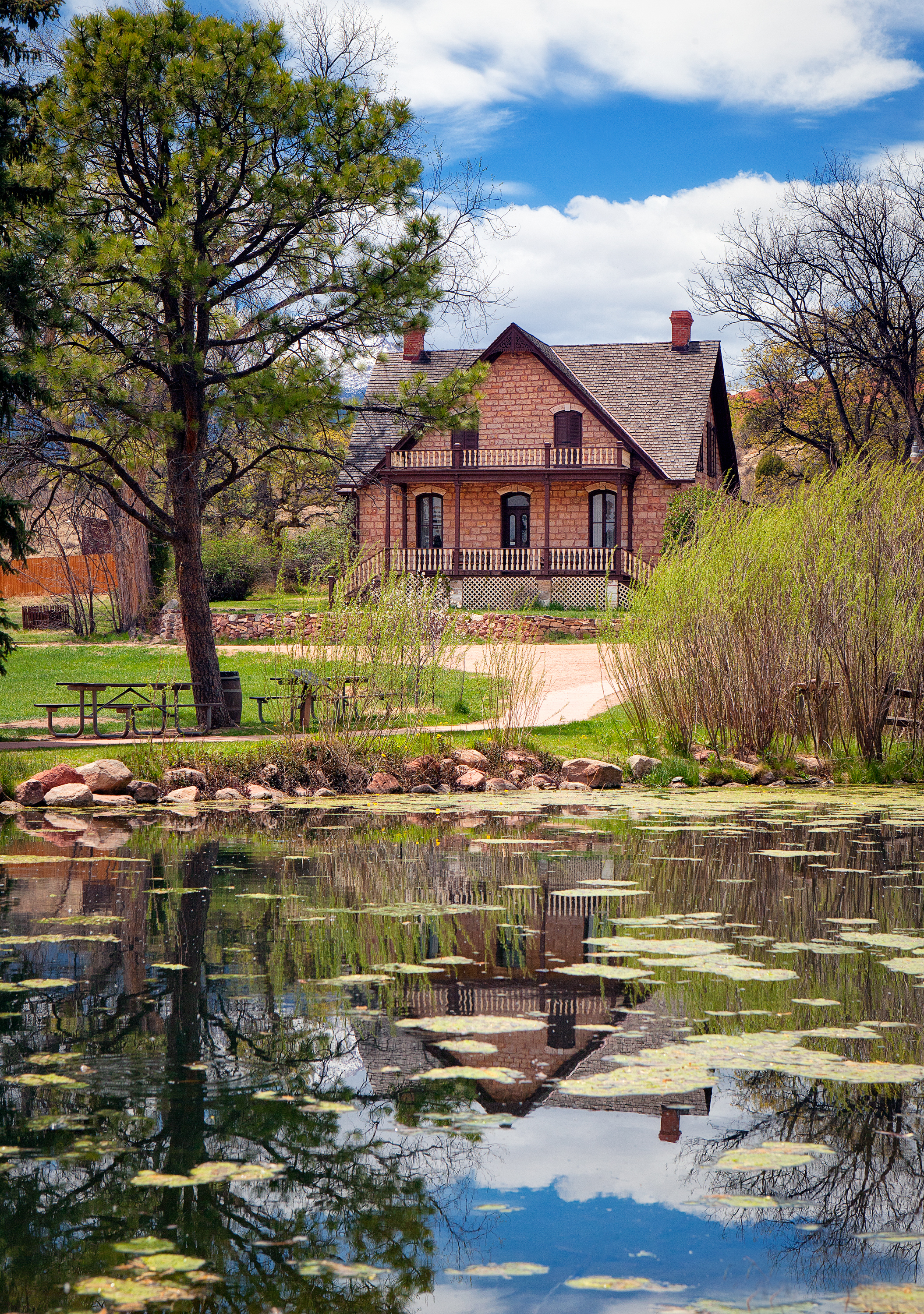 Rock Ledge Ranch Historic Site: a historic home sits behind a pond reflecting the trees and sky