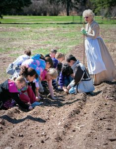 children planting crops in a plowed field with a woman dressed in period costume watching over them