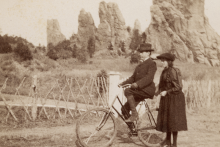 woman stands next to a man on a bike. Large rocks in the background.
