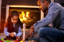 A little girl and her dad play with blocks in front of the fireplace