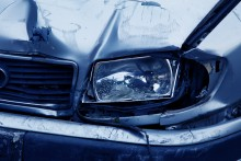 A damaged car appears to have extensive headlight damage