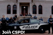 """A police car with several officers surrounding it, posing for a photo. Caption reads """"join CSPD"""""""