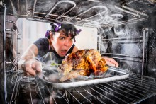 A woman pulling a smoking turkey out of the oven