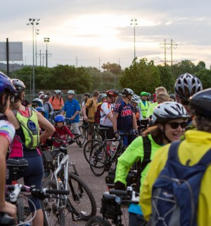 A large group of bicyclists gathered together in the parking lot getting ready to ride. Morning sky with the sun rising in the background