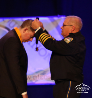 Chief Niski puts medal on Cem Duzel
