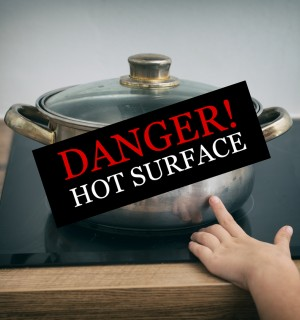 """A child's hand reaching for a pot on the stove. Words read """"Danger! Hot Surface"""""""