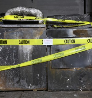blackened burnt clothes washer and dryer with yellow caution tape over them