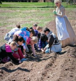 Farm woman watching children plant seeds in the garden at Rock Ledge Ranch