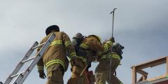 Firefighters on roof of building