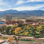 aerial view of acacia park. downtown building and mountains in the background. Some trees have golden leaves.