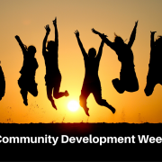 """Silhouette of six people jumping with the sun setting behind them in a golden sky. text says """"community development week'"""
