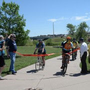 A group of bike riders break through a red ribbon stretched across the new bike path