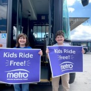 """two middle school age kids (a boy and a girl) stand in front of a MMT bus. They are holding purple signs with white writing that says """"kids ride free"""" with an MMT logo."""