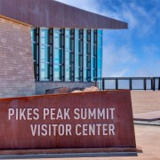 Pike Peak Summit Visitor Center sign. Outdoor viewing platform and wall of windows on the visitor center in the background.