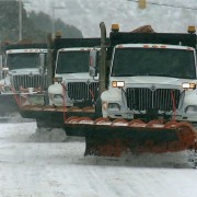three snowplows plowing in tandum.