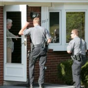 two police officers talk to woman at front door of her home during evacuation drill