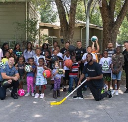 kids holding sport balls pose for photo with officers