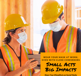 "two constructions workers wearing bright orange safety vests and hard hats are talking, while wearing a mask. ""Wear your mask at work even with close coworkers."" Small acts, big impacts."" Use # small acts to share your stories on social media."