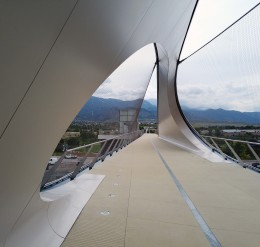 looking down the path of the bridge. on the left, a curved wall that loops overhead and to the other side. there are large curved gaps in the wall on each side. The effect is a wave that moves from one side of the bridge to the other.