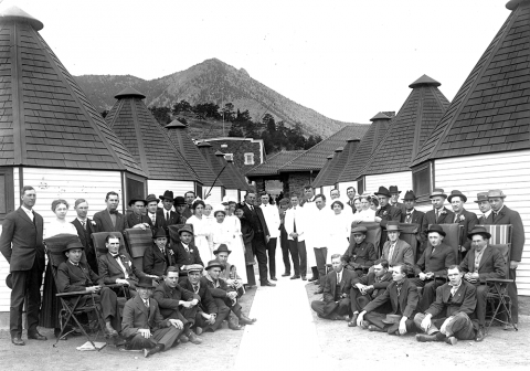 black and white photo of a large group of people posing in front of a wide walkway lined on both sides by small, round, white buildings with pointy black roofs.