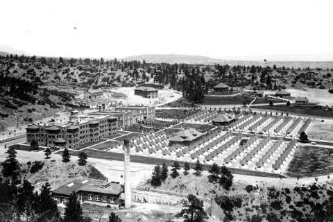 back and white aerial photo of a compound lined with walls. A large multi story building in on the left side, and the right two thirds are filled with hundreds of smaller, identical buildings.