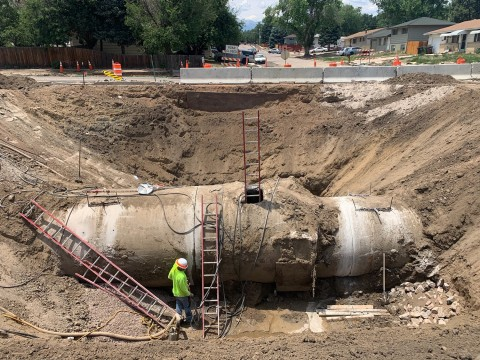 massive hole and cement pipe approximately 10-12 feet tall being installed underground