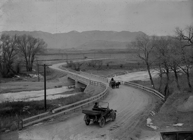 a model tee car and wagon pulled by two horses moving toward each other on a two lane dirt road. A bridge over a large creek. The dirt road winds into the the background with mountains also  in the background