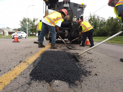 three people smooth black asphalt in a large pothole to prepare for steam rolling. A large truck that spreads the asphalt is in the background. Orange cones direct traffic away from the crew.