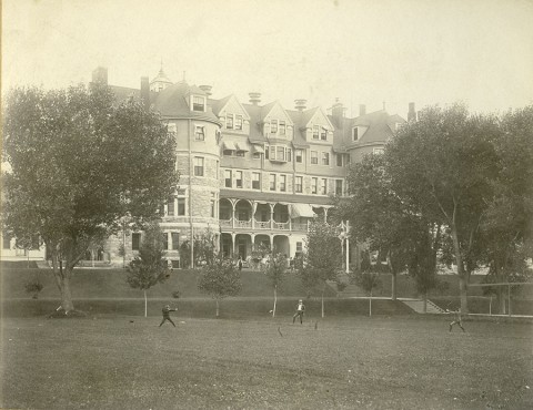 historic photo. Large hotel in the background. people are doing archery in a large, open, grassy field. Large trees line the filed between the field and the hotel.
