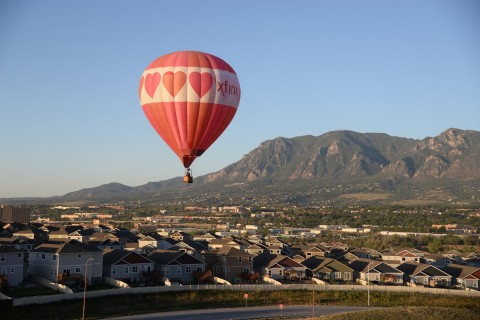 red hot air balloon hovering over neighborhood. Cheyenne Mountain in the background.