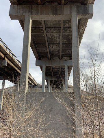 view looking up at the underside of a bridge