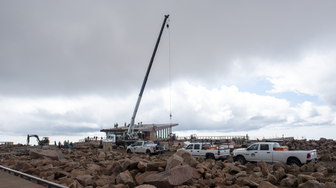 boulder field. A very tall crane is moving a large piece of metal. Summit visitor center in the background.