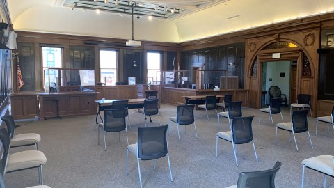 council chambers looking toward the council's seating. resident seating chairs spaced six feet apart. Plexiglas surrounds the dias due to COVID-19  .