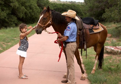 a man holds the lead of a brown horse as a young girl reaches up to pet the horse's nose. They are standing on a paved trail in Garden of the Gods