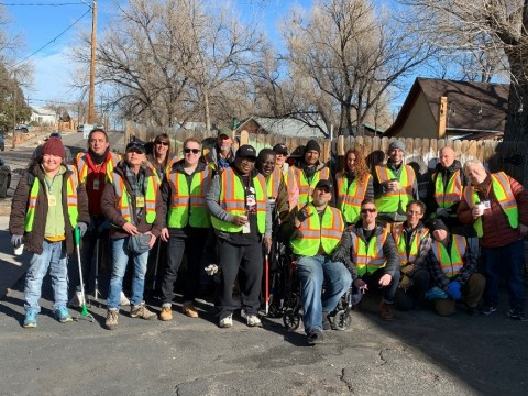 My City Project volunteers wearing bright work vests and holding trash pickup tools.
