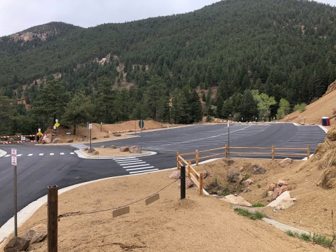 view of newly paved parking lot from High Drive. Tree covered canyon walls in the background.
