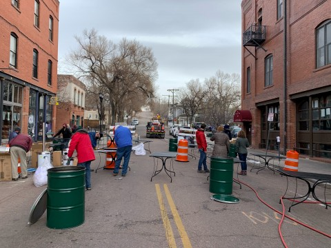 people setting up outdoor dining in the street