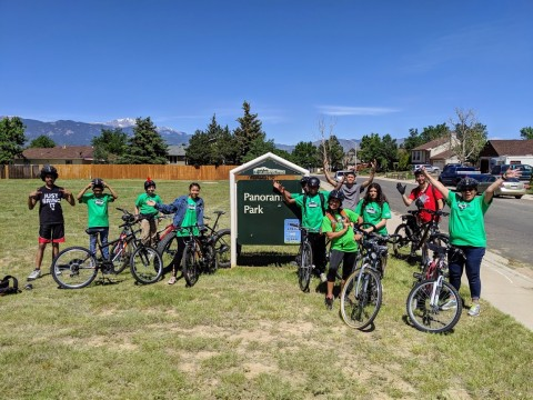 group of bike riders wearing green shirts and standing with their bikes in front of the Panorama Park sign.