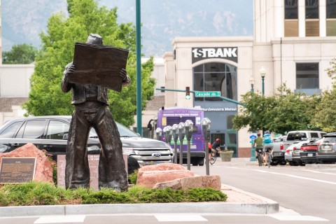 statue of cowboy reading newspaper