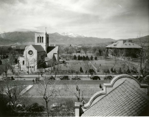 historic photo of Colorado College. A few large buildings are in the middle of landscaped grassy areas with sidewalks and trees. people dot the area. Pikes Peak in the background.