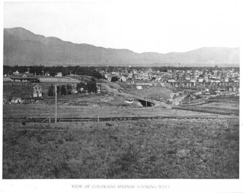 historic black and white photo. houses in a neighborhood on the right side. larger buildings dot the area on the right side. Dirt roads. Pikes peak in the background