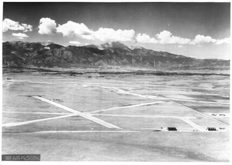 black and white photo of airport taxiways and runways crisscrossing the flat landscape. Mountains and pikes peak in the distance