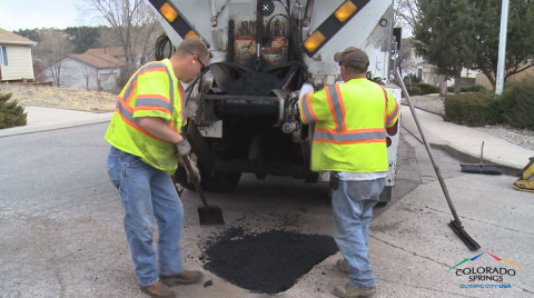 two men fill pothole